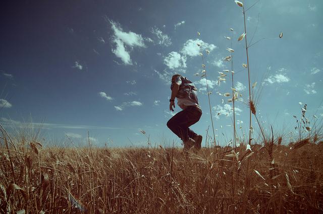 Un homme saute dans un champ.