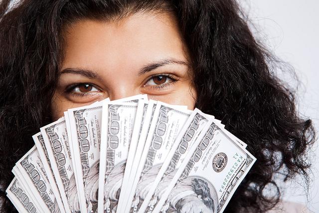 Femme tenant un éventail de billets de 20 dollars.