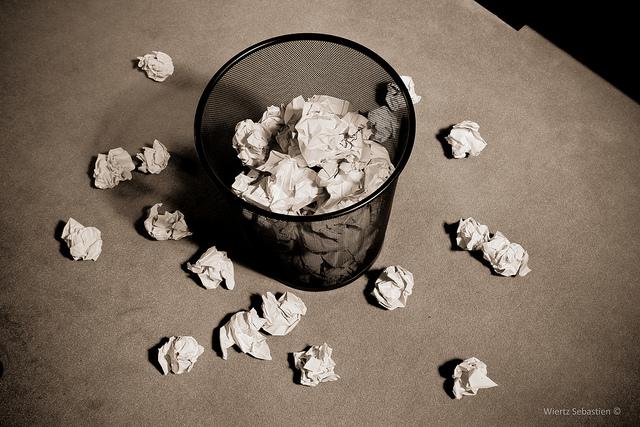 Poubelle de bureau remplie de papiers froissés, des boules tombées autour.