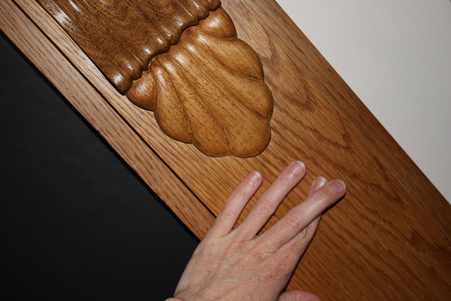 Une main avec les doigts croisés sur une rambarde en bois.