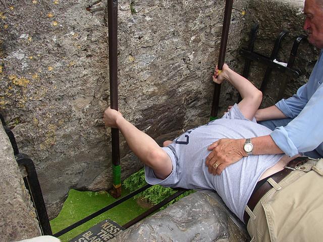 Photographie d'un visiteur embrassant la pierre du château de Blarney.