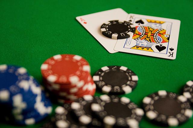 Jetons et cartes de poker sur un tapis vert.