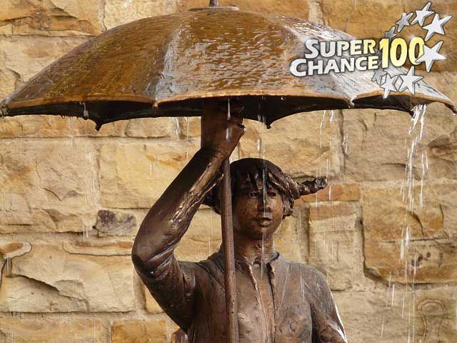Une fontaine sous forme de statue tenant un parapluie.