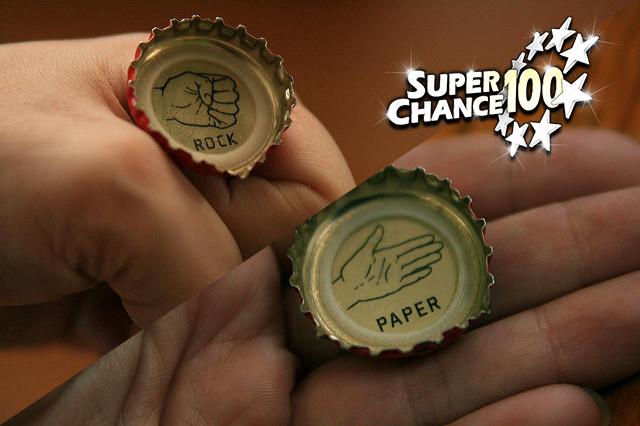 Photographie de mains tenant des capsules de bouteilles gravées avec des signes du jeu chifoumi.