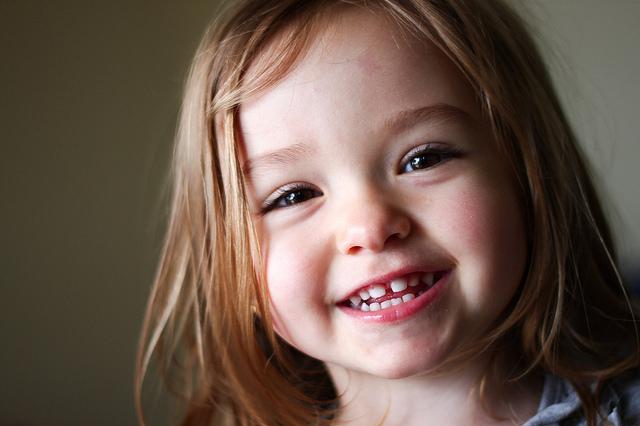 Photographie d'une petite fille affichant ses dents en souriant.