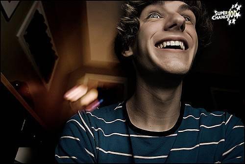 Photographie d'un homme souriant en contre-plongée.