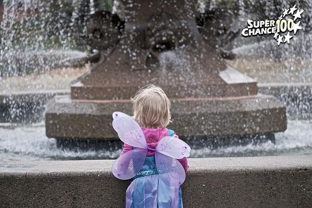 Photographie d'une petite fille en costume de fée devant une fontaine.