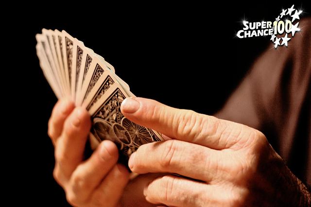 Photographie d'un jeu de cartes dans la main d'une personne.