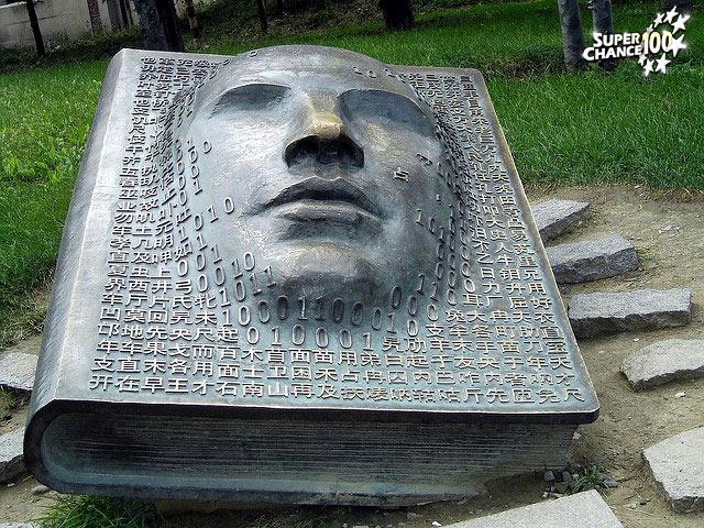 Structure métallique en forme de livre avec en couverture des données numériques et un visage.