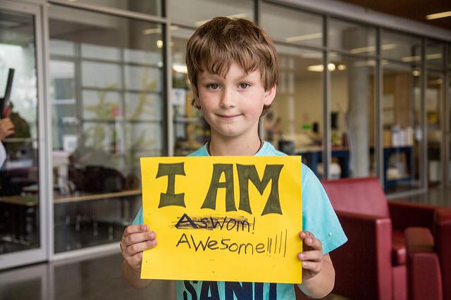 """Photographie d'un garçon tenant une pancarte avec le message """"je suis génial""""."""