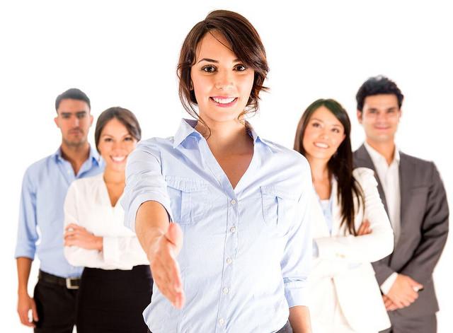 Photographie d'un groupe de personnes bienveillantes avec une femme au premier plan tendant la main.