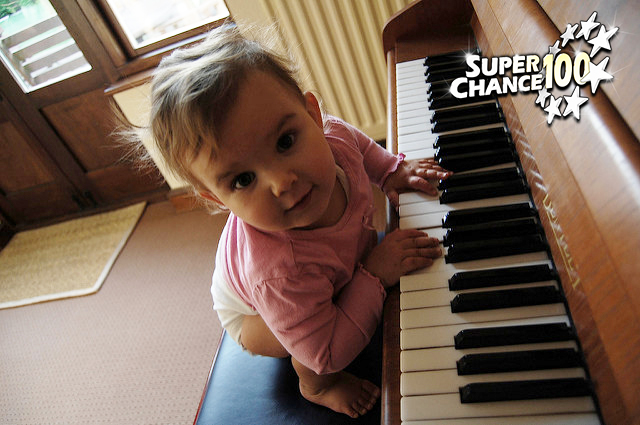 Photographie d'un bébé en train de jouer du piano.