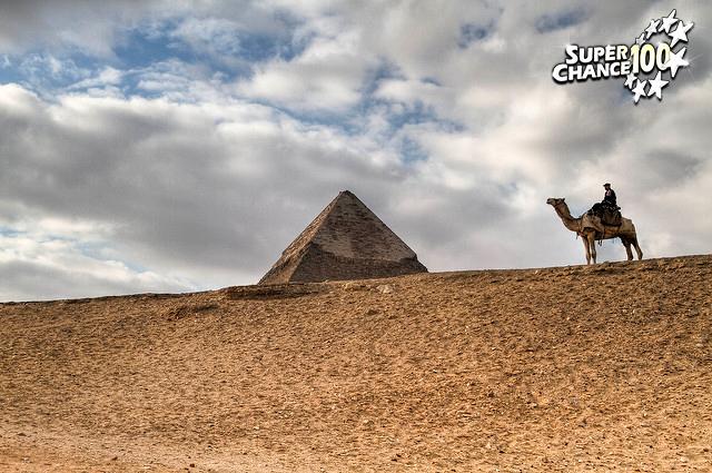 Photographie d'une paysage désertique avec un homme à dos de chameau devant une pyramide.