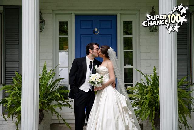 Photographie d'un couple fraîchement marié devant le domicile conjugal.