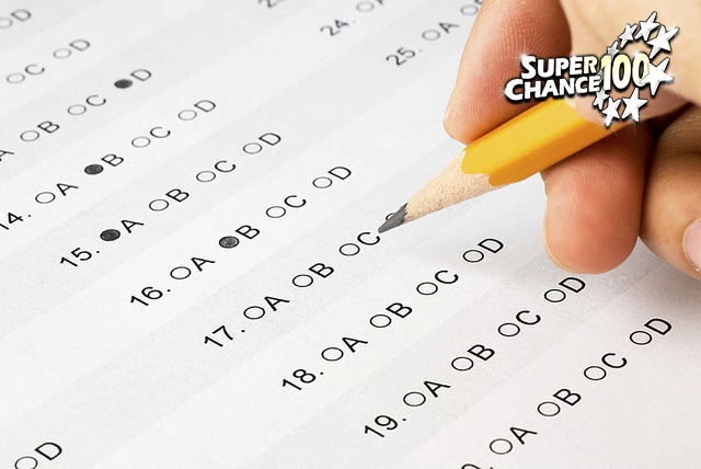 Photographie d'un questionnaire en gros plan avec la main d'un individu en train d'y répondre avec un crayon de papier.