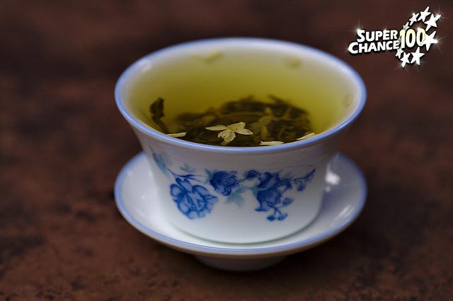 Photographie d'une tasse de thé avec des feuilles flottant à la surface du breuvage.