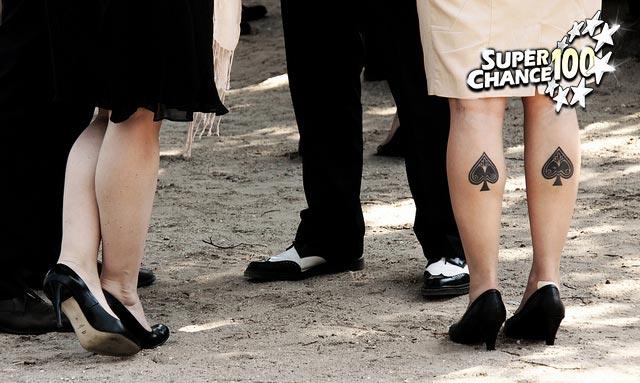 Photographie de plusieurs paires de jambes dont une avec des tatouages en forme d'as de pique sur chaque mollet.
