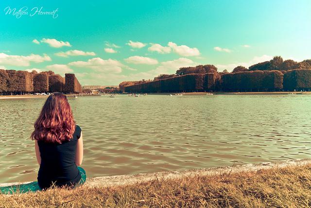 Femme assise devant un lac, regardant au loin.