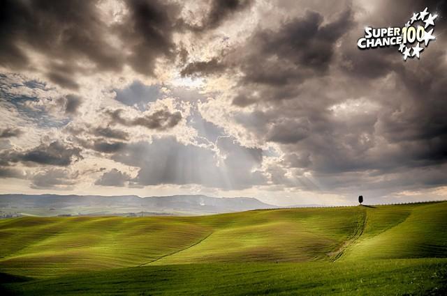 Trouée de lumière à travers des nuages au dessus d'une plaine verdoyante.