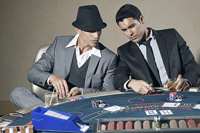 Deux hommes discutent devant un jeu de poker.