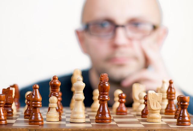 Un homme se tient le visage devant un jeu d'échecs.
