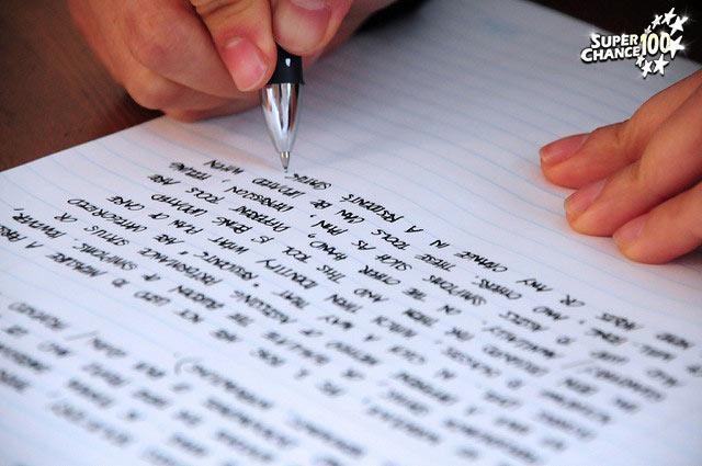 Une personne écrit avec un stylo noir sur une feuille.
