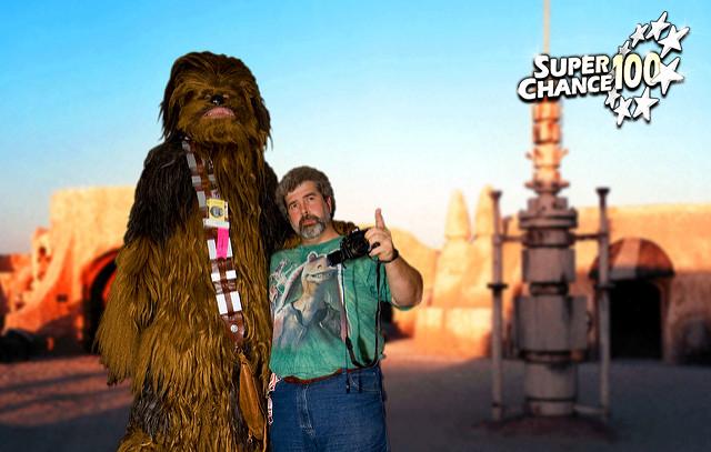 Georges Lucas accompagné d'une personne déguisé en Chewbacca dans un décor du film Star Wars.