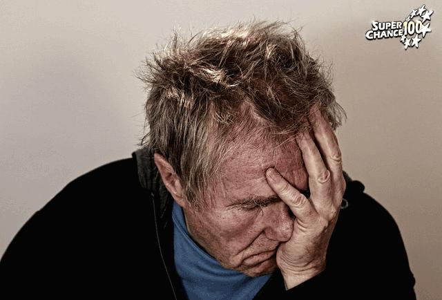 Un homme tient son visage dans sa main, en signe de désespoir.