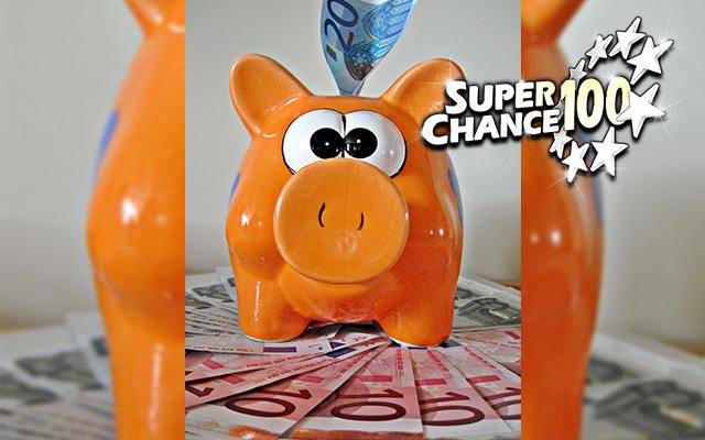 Photographie d'une tirelire en forme de cochon posée sur un tas de billets.