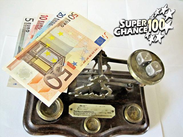 Photographie d'un tas de billets et d'une paire de dés sur une balance.