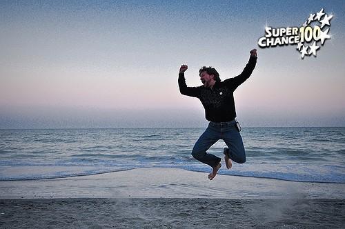 Un homme saute de joie sur une plage, il a gagné à l'EuroMillion.