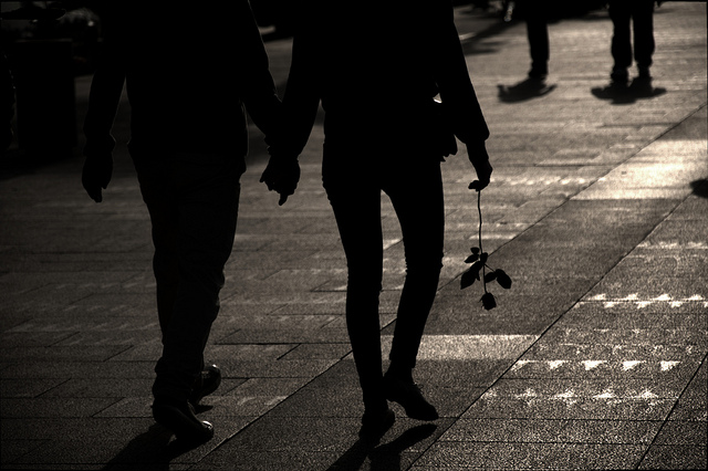 Deux personnes se tenant par la main et marchant dans la rue.