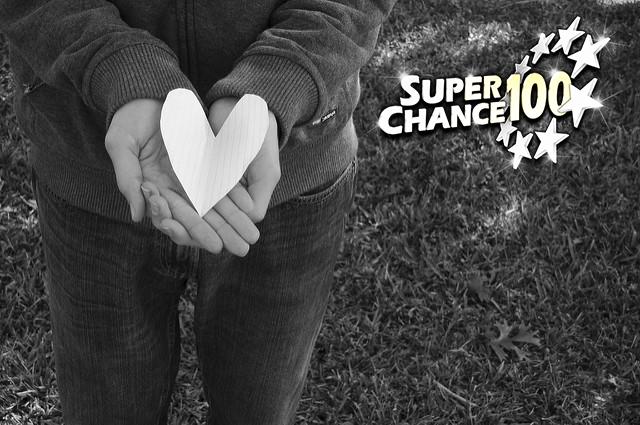 Cœur en papier posé dans une main pour symboliser le partage et la solidarité.