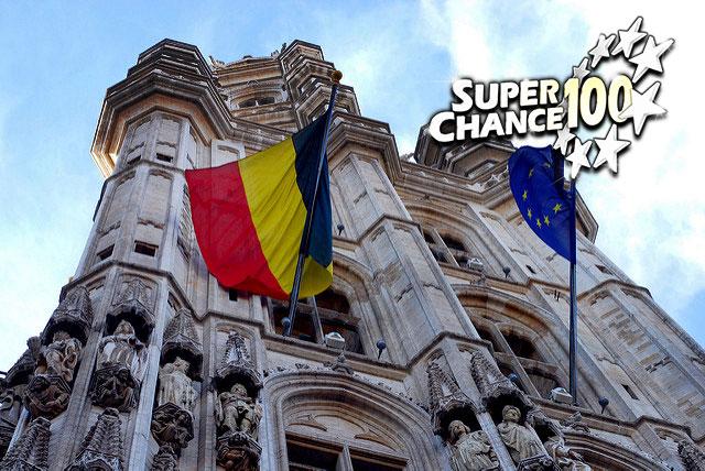 Photographie d'une cathédrale avec les drapeaux de la Belgique et de l'Europe.