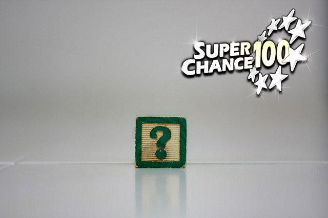 Photographie d'un bout de carton sur lequel est dessiné en vert un point d'interrogation.