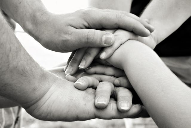 Une famille fait une pile de mains.