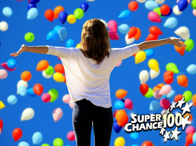 Femme de dos levant les bras, devant pleins de ballons colorés.