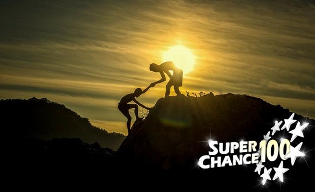 Enfant en train d'aider son ami à grimper, devant un coucher de soleil.