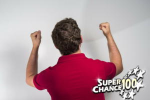 Homme de dos, levant les bras pour célébrer une victoire.