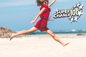 Jeune femme qui saute sur une plage paradisiaque après avoir gagné l'Euro Millions.