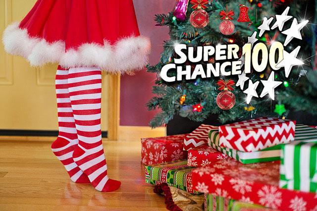 Sapin de Noël avec des cadeaux et la Mère Noël en chaussettes à rayures.
